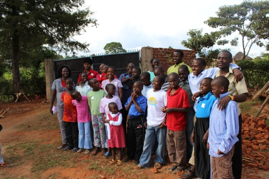 the children smile outside their new home